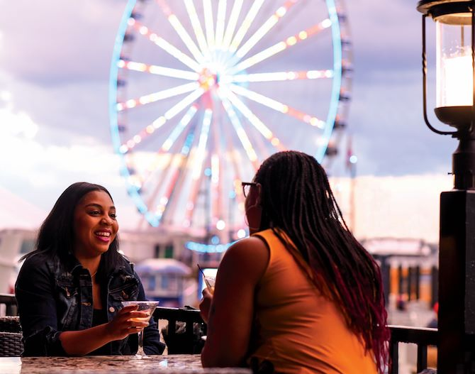 Young women having cocktails by Capital Wheel in National Harbor