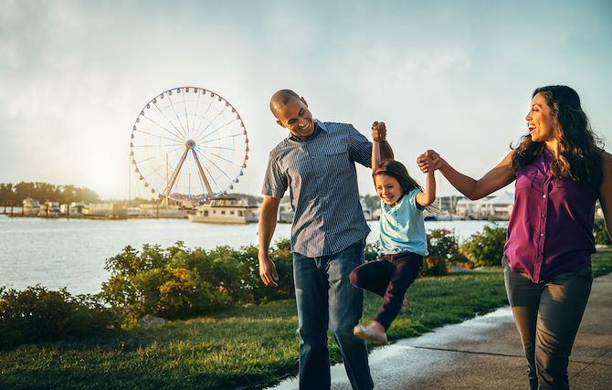 Family holding hands along National Harbor Waterfront near Gaylord National Resort