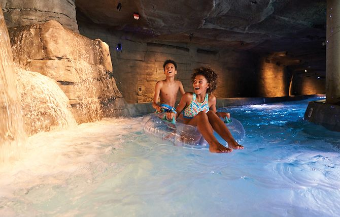 Two kids on tubes in cave tunnel at SoundWaves lazy river