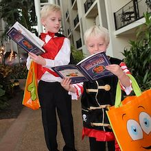 Two young boys in costumes with halloween scavenger hunt booklets in atrium at Gaylord Opryland