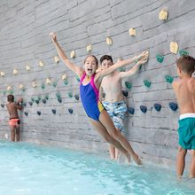 Young girl jumping in water from SoundWaves Rock Wall