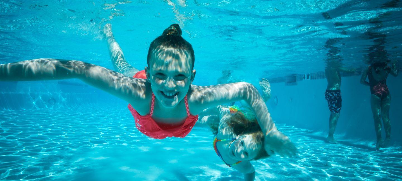 Kids swimming underwater at Arapahoe Springs Water Park at Gaylord Rockies in Aurora, CO