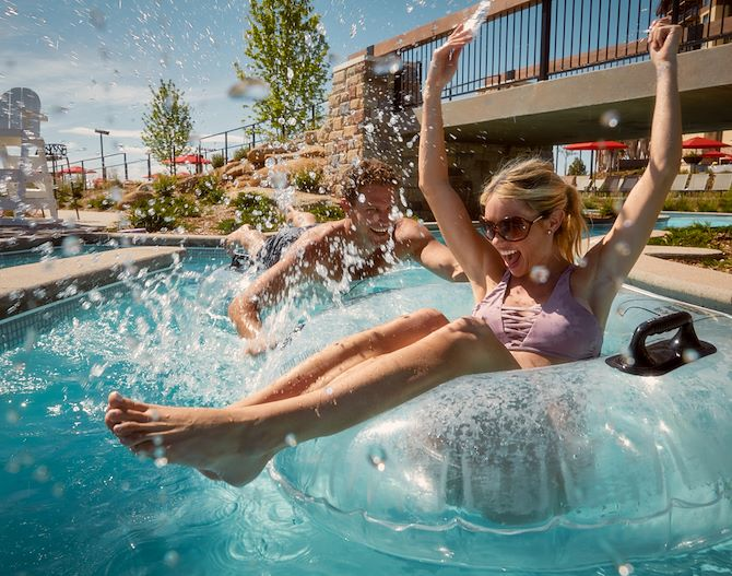 Woman on clean inner tube with hands up at Arapahoe Springs Lazy River at Gaylord Rockies