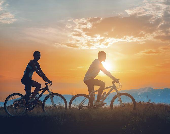 Person Mountain Biking with Rocky Mountains on the Horizon