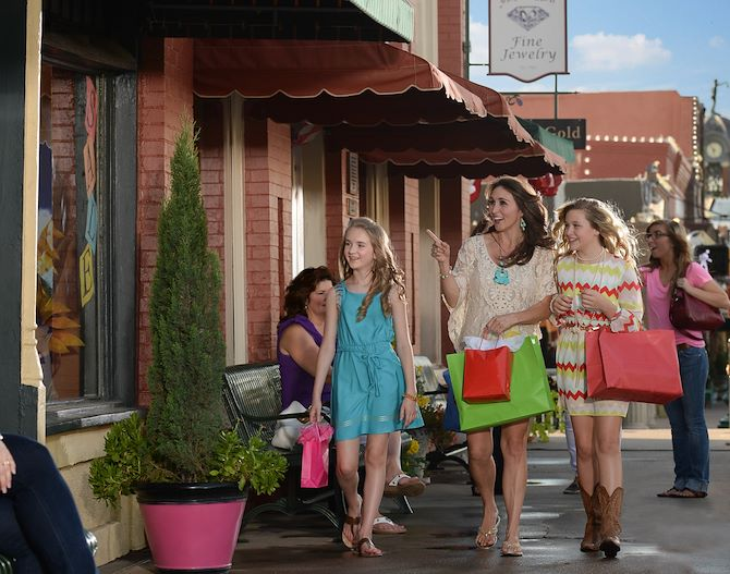 Woman and two young girls walking on sidewalk with shopping bags in downtown grapevine, minutes from Gaylord Texan