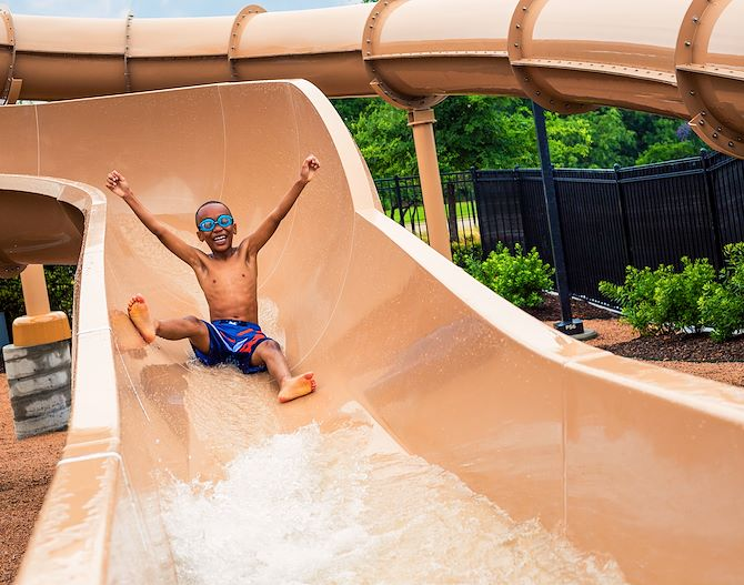 Kid with arms up on Paradise Springs Water Slide