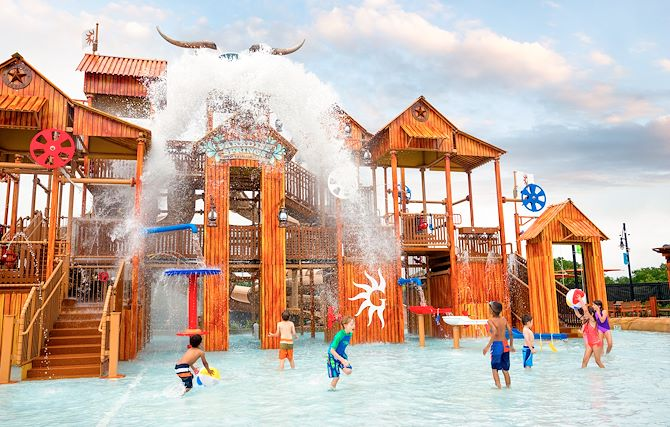 Kids in water in front of Paradise Springs Treehouse structure at Gaylord Texan