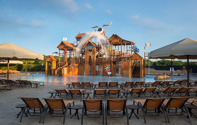 Paradise Springs Pool lounge chairs in front of playhouse structure at Gaylord Texan