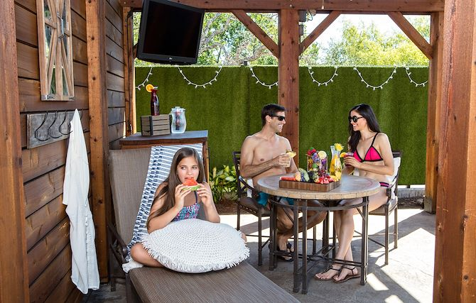 Girl eating watermelon with family in private cabana inside Paradise Springs at Gaylord Texan