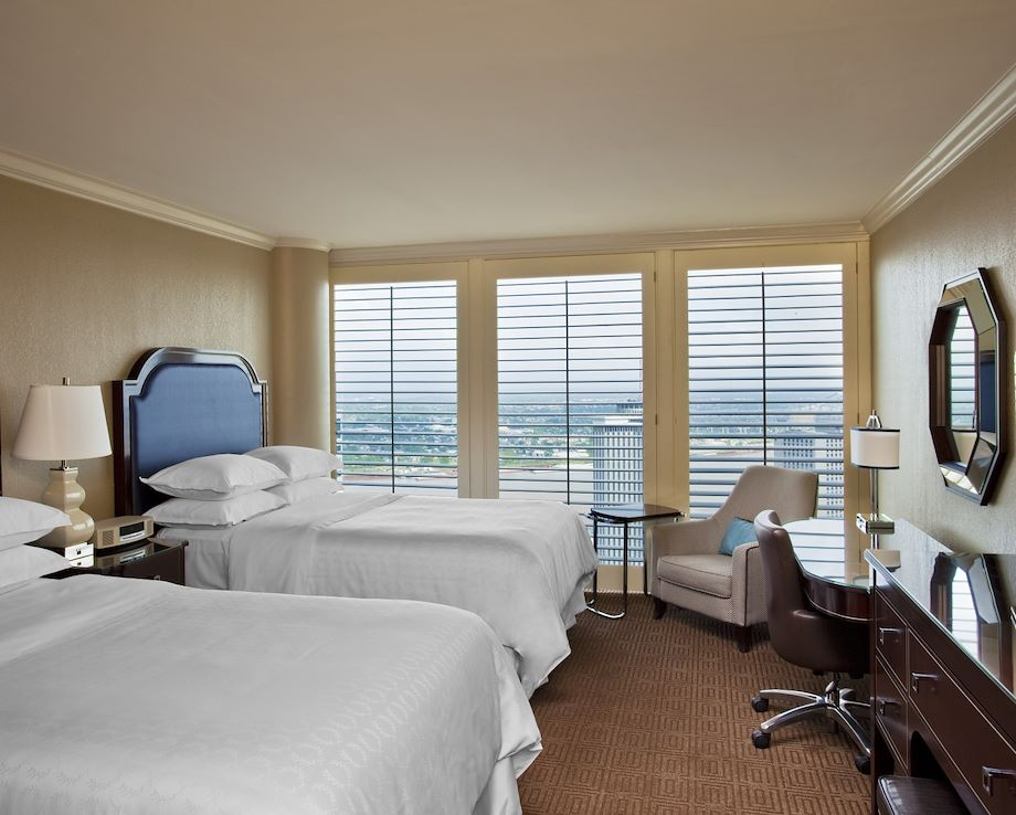 Image of two beds in a hotel room with a view over the city