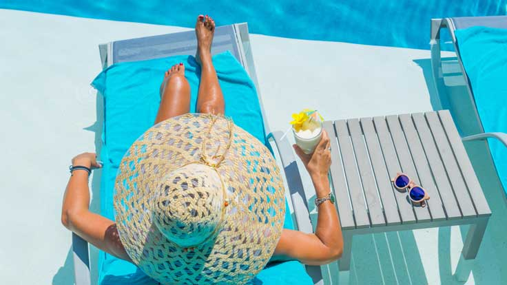 Woman sitting on a poolside chaise lounge holding mixed drink