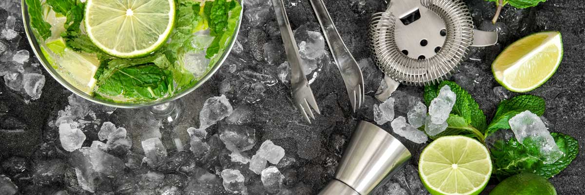 Arrangement of mint leaves and limes on crushed ice with bar tools